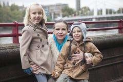 Porträt der jungen Frau mit den Kindern, die draußen lächeln Lizenzfreie Stockbilder