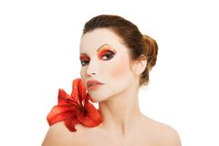 Porträt der jungen Frau mit roter Lilienblume Stockbild