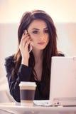 Porträt der jungen Frau mit Tasse Kaffee, Laptop und beweglichem pH Lizenzfreie Stockfotos