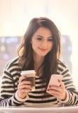 Porträt der jungen Frau mit Tasse Kaffee und Handy Stockbild