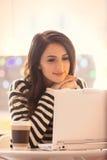Porträt der jungen Frau mit Tasse Kaffee und Laptop Lizenzfreie Stockbilder