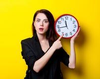 Porträt der jungen Frau mit Uhr Stockfotografie