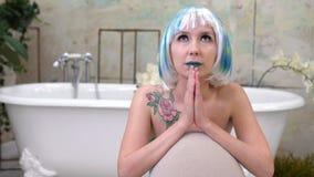 Porträt der jungen Frau in der Perücke betend im Badezimmer Stockbilder
