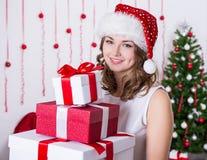 Porträt der jungen Frau in Sankt-Hut mit Haufen von Geschenken nahe Stockfotos