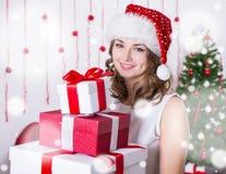 Porträt der jungen Frau in Sankt-Hut mit Haufen von Geschenken nahe Lizenzfreie Stockfotografie