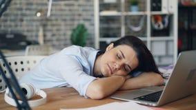 Porträt der jungen Frau schlafend auf dem Schreibtisch, der sich zuhause bei der Arbeit entspannt stock footage