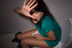 Porträt der jungen Frau schreiend in der Toilette zur Kamera Lizenzfreie Stockfotos