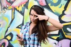 Porträt der jungen Frau sitzend an der Graffitiwand Lizenzfreies Stockbild