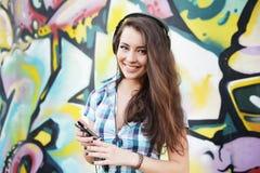 Porträt der jungen Frau sitzend an der Graffitiwand Lizenzfreie Stockfotos