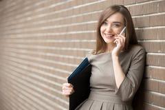 Porträt der jungen Frau sprechend am Telefon und Kamera O betrachtend Stockfoto