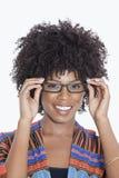 Porträt der jungen Frau in tragenden Gläsern der afrikanischen Druckkleidung über grauem Hintergrund Lizenzfreies Stockbild