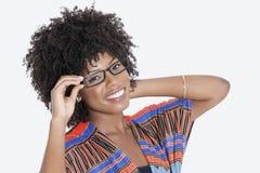 Porträt der jungen Frau in tragenden Gläsern der afrikanischen Druckkleidung über grauem Hintergrund Lizenzfreie Stockfotografie