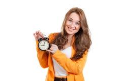 Porträt der jungen Frau zeigend auf einen Wecker Lizenzfreies Stockbild