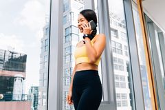 Porträt der jungen geeigneten Frau, die auf dem Schleifstein an der hohen Aufstiegsturnhalle spricht Weibliches Eignungsmodellbil lizenzfreie stockfotos