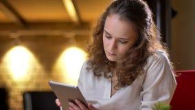 Porträt der jungen gelockten Geschäftsfrau, die ernsthaft in Tablette aufpasst und ihre Augen zur Kamera im Büro anhebt stock video