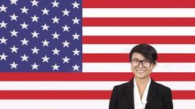 Porträt der jungen Geschäftsfrau lächelnd über amerikanischer Flagge stockfoto