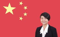 Porträt der jungen Geschäftsfrau lächelnd über chinesischer Flagge lizenzfreie stockbilder