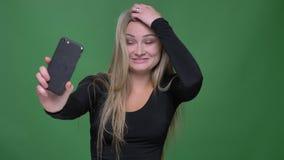 Porträt der jungen Geschäftsfrau in der schwarzen Bluse froh sprechend im videochat auf Smartphone am grünen Hintergrund stock video