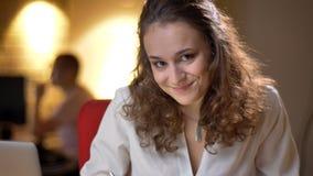Porträt der jungen Geschäftsfrau smilingly und schüchtern aufpassend in Kamera auf Bürohintergrund lizenzfreie stockbilder
