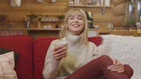 Porträt der jungen hübschen Frau, die eine Tasse Tee und das Lachen hält Stockfotografie