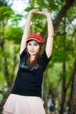 Porträt der jungen hübschen Frau, die Hände oben gegen Baum anhält Stockbilder