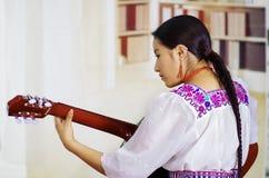 Porträt der jungen hübschen Frau, die schöne traditionelle Anden-Kleidung, setzend mit dem Akustikgitarrespielen trägt hin lizenzfreie stockbilder