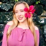 Porträt der jungen hübschen Jugendlichen, die mit hawaiischer Blume im Haar lächelt Stockbild
