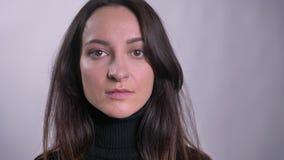 Porträt der jungen kaukasischen brunette Frau, die direkt in Kamera auf grauem Hintergrund aufpasst stock video