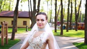 Porträt der jungen lächelnden Braut, die um Bräutigam im grünen Park geht stock video
