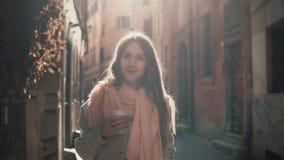 Porträt der jungen lächelnden Frau, die Kamera betrachtet Glückliches attraktives Mädchen, das in der Morgenstraße, tuend herauf  Lizenzfreies Stockbild