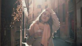 Porträt der jungen lächelnden Frau, die Kamera betrachtet Glückliches attraktives Mädchen, das in der Morgenstraße, tuend herauf  Stockfoto