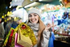 Porträt der jungen lächelnden Frau im Mantel, der an Weihnachtsmesse aufwirft Lizenzfreie Stockbilder