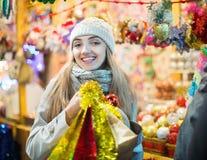 Porträt der jungen lächelnden Frau im Mantel, der an Weihnachtsmesse aufwirft Lizenzfreies Stockfoto