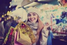 Porträt der jungen lächelnden Frau im Mantel, der an Weihnachtsmesse aufwirft Lizenzfreie Stockfotos