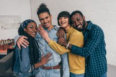Porträt der jungen lächelnden Gruppe multiethnischer Freundumfassung lizenzfreie stockbilder