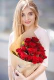 Porträt der jungen lächelnden Schönheit mit Blumen Lizenzfreies Stockfoto