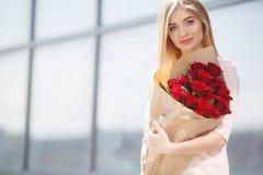 Porträt der jungen lächelnden Schönheit mit Blumen Stockfoto