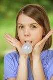 Porträt der jungen lustigen Frau mit Birne im Mund Lizenzfreies Stockfoto