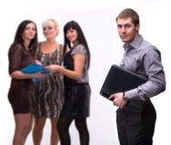 Porträt des jungen Mannes mit Laptop mit Gruppe von Personen Stockfotografie