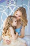 Porträt der jungen Mutter hält ihre kleine Tochter auf einem Stuhl Lizenzfreies Stockbild