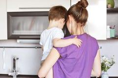 Porträt der jungen Mutter hält kleinen Sohn auf Händen, stehen zurück zusammen, Arbeit über die Küche und geht, köstliches Abende lizenzfreies stockfoto