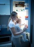 Porträt der jungen Mutter nach Lebensmittel im Kühlschrank nachts suchend, um ihr kleines Baby einzuziehen Lizenzfreies Stockfoto