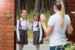 Porträt der jungen Mutter wellenartig bewegend zu ihren Kindern, die zur Schule verlassen stockbilder