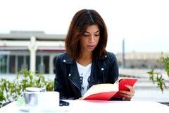 Porträt der jungen reizenden Frau, die ein gutes Buch beim Sitzen am Tisch in der Kaffeestubeterrasse genießt lizenzfreie stockbilder