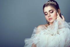 Porträt der jungen schönen Braut im Diadem, das flaumigen Rock ihres Hochzeitskleides zu ihrer Brust drückt lizenzfreies stockbild