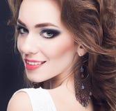 Porträt der jungen schönen Brunettefrau im Schmuck, der O steht Stockbilder