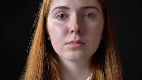 Porträt der jungen schönen ernsten Frau, welche die Kamera, besetzt, lokalisiert auf schwarzem Hintergrund betrachtet stock footage