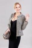 Porträt der jungen schönen Geschäftsfraublondine im schwarzen Kleid und mit Tasche auf grauem Hintergrund Lizenzfreies Stockfoto