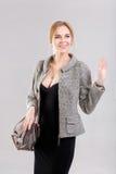 Porträt der jungen schönen Geschäftsfraublondine im schwarzen Kleid und mit Tasche auf grauem Hintergrund Stockbild