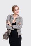 Porträt der jungen schönen Geschäftsfraublondine im schwarzen Kleid und mit Tasche auf grauem Hintergrund Stockfoto